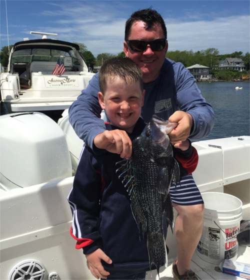 Boy and his father on charter fishing boat holding sea bass that the boy caught