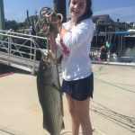 Girl holding large striped bass that she caught